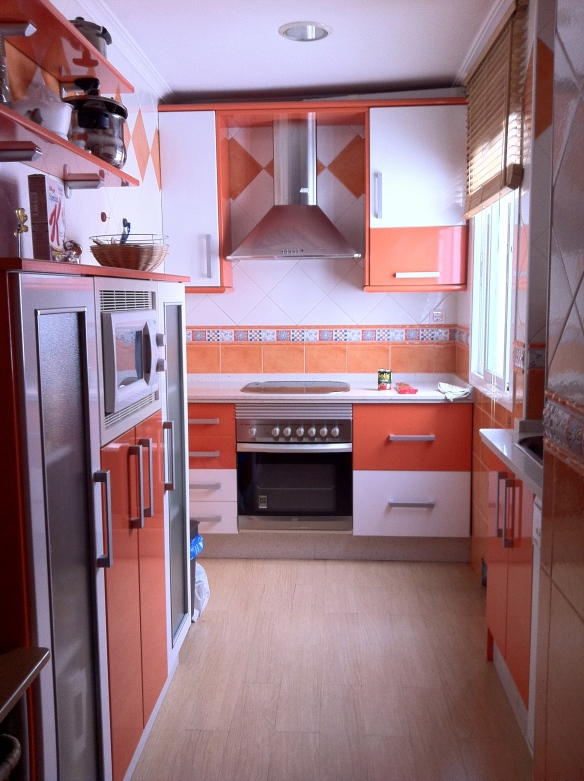 My kitchen, all orange and white and tiled with a light wooden floor.
