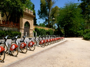 A row of bright red Sevici bikes lined up before the Jardines de Murillo