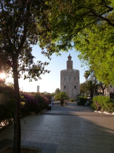 The Torre de Oro framed by summer leaves