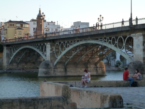 People picnic by the river, overlooking the bridge and its memorable circle architecture